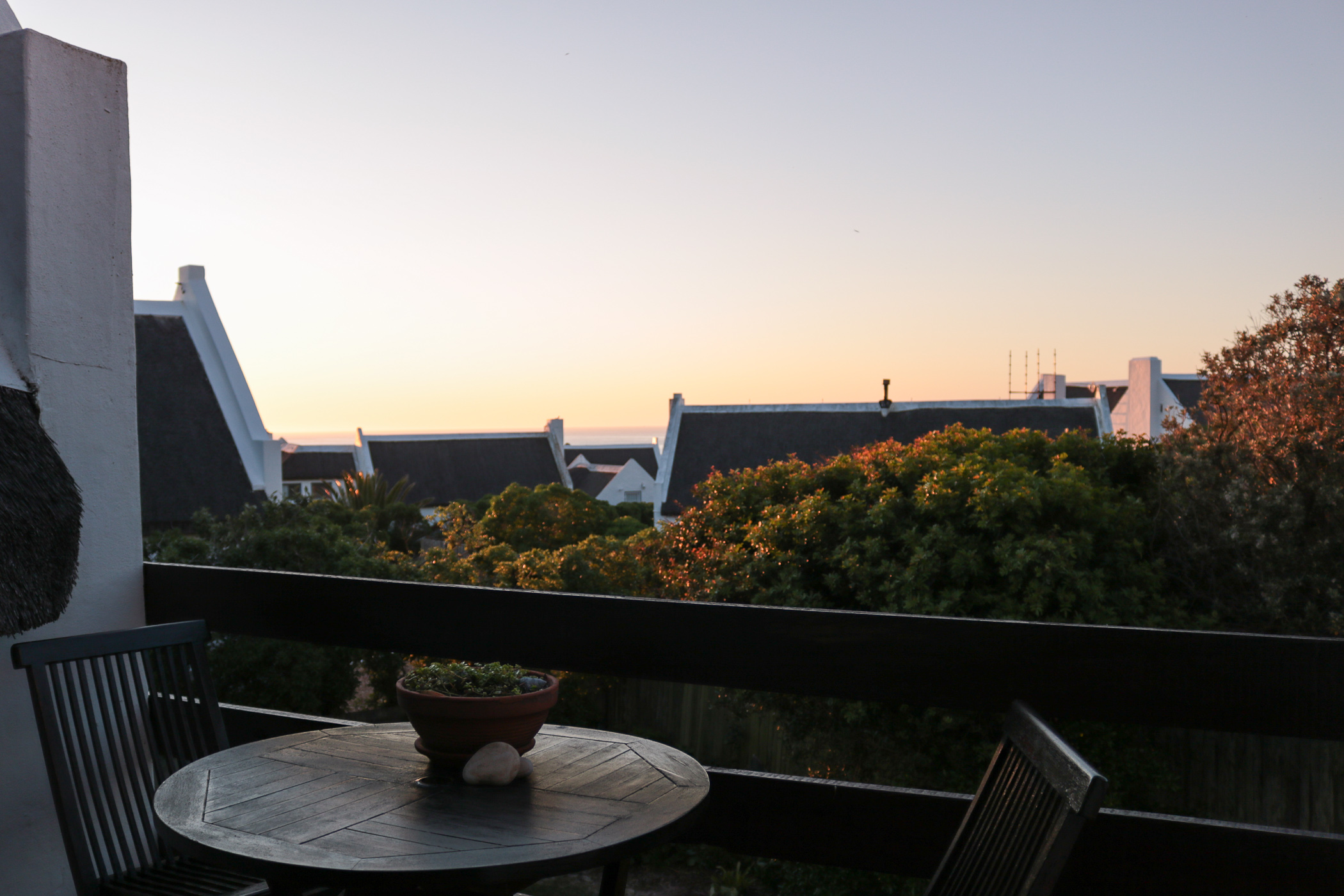 View of the thatch roofs and the ocean at sunset from balcony